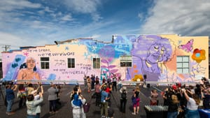 A wide shot of the mural with an audience in front of it, with a few people near a podium.