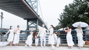 A group of dancers pose, all in white. Everyone has umbrellas, one of them is open. The Ben Franklin bridge is behind them.