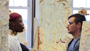 Brown, a Black woman, and Goraczko, a white man, look towards each other in a well-lit room, art canvases are around them.