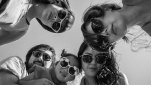 In black and white, three women, one girl, and a man, presumably Asian American, look down at the camera wearing sunglasses.