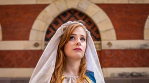 Actor Rachel Brodeur. She has long red hair and wears a flowing light-colored linen headdress like images of the Virgin Mary