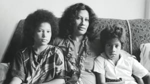 Merata Mita sits with two her children in a black and white portrait.