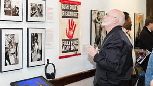 AIDS Library co-founder John Cunningham takes in the art and messages at 'Still Fighting for Our Lives.' (Photo by Holly Clark)