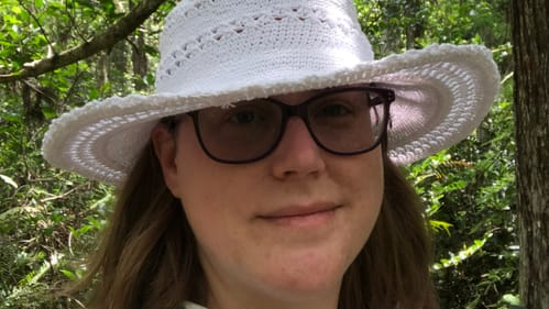 A selfie of Alaina, a 37-year-old white woman, in a green cypress swamp. She wears sunglasses and a touristy white hat.