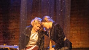 Two white women actors lean heads tenderly together, inside a glittery curtain. They wear a mix of leather, velour, & satin