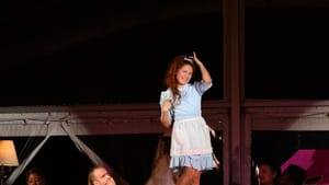 Jenna Kuerzi, a white woman, as Alice in a blue dress & white apron. She poses on a table with ensemble members around her