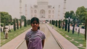 Indian American writer Christina Anthony as a child, pictured in front of the Taj Mahal. She wears purple overalls