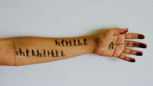 Refugee Basel Zaraa draws images of displacement on visitors' arms. (Photo courtesy of the artist.)