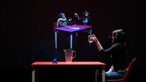 On a black background, a woman at a table lifts a glass, and appears to sit beside another person in a projected image nearby