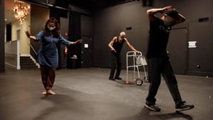 Three dancers in a rehearsal space. Solomons has a walker. Lin has his hands behind his back. Chakravorty steps with arms out