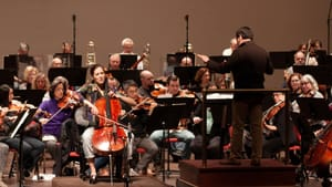 An unusual ongoing dialogue: Cellist Camille Thomas, Maestro David Amado, and the orchestra in rehearsal for DSO's 'False Starts' program. (Photo Courtesy of Delaware Symphony Orchestra.)