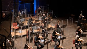 DSO members wear masks, sit behind plexiglass, and play for a nearly empty house, but livestreaming has upsides for audiences. (Photo courtesy of Delaware Symphony Orchestra.)