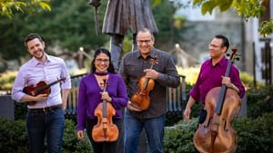 Four musicians pose together, trees and bushes in the background, with a cello, viola, and two violins at hand.