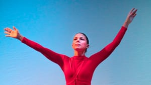 Dancer Kate Lombardi, a white woman, holds out her arms onstage. She wears a long, flowing red dress with long tight sleeves.
