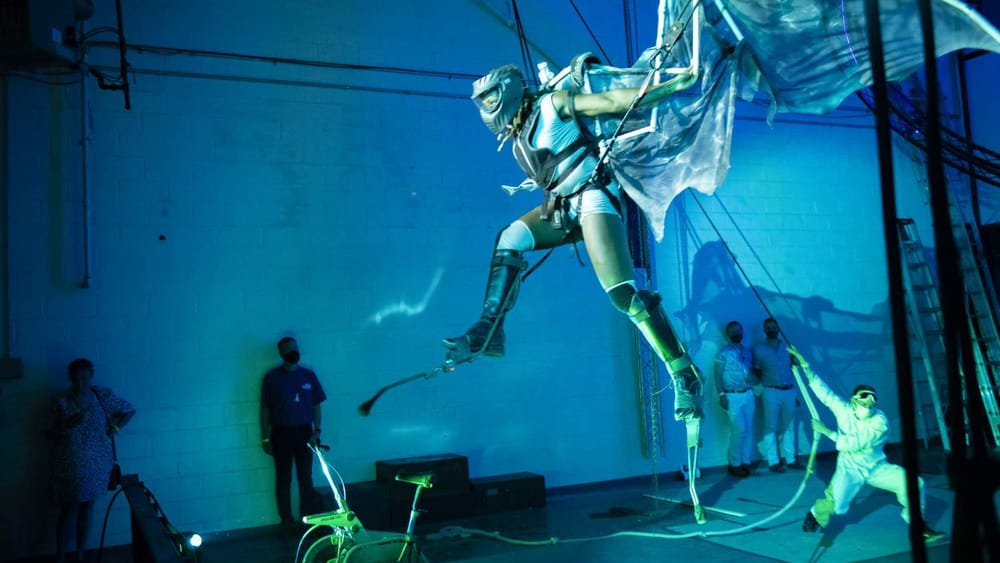 In dramatic blue lighting, actor Desirée Hall seems to fly in a dragon costume with giant wings, beside a cinderblock wall.