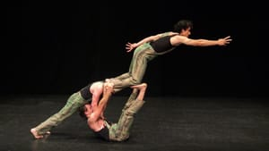 A living acrobatic sculpture of three men, two on the floor and one aloft with his feet and knees anchored on the others