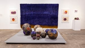 An art gallery view of 11 decorative balls in different colors and textures, from baseball size up to large bowling balls