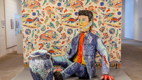 A large colorful ceramic sculpture of a man in a blue suit & orange tie sitting on the ground, his feet tipping an urn over