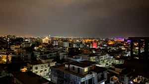 A nighttime city view in Islamabad, Pakistan, with dozens of boxy white buildings and colorful lights under a cloudy sky.