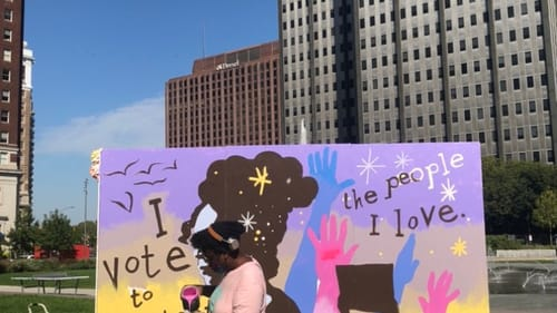 Artist Kah Yangni works on a mural that reminds us our vote is a way to show our love. (Photo by Alaina Johns.)