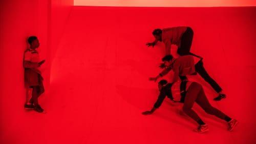 On a red-lit stage, four Black men crawl menacingly toward a Black boy.