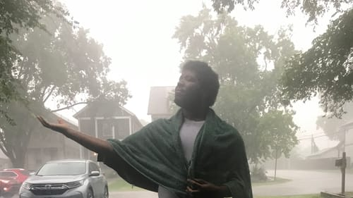 Kyle, a Black man, stands outside in the pouring rain, his arm extended, his palm open and head tilted, embracing the storm