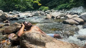 Kyle, a Black man, lies against large rocks in a river, looking up to the sunny sky while wearing sunglasses and swim trunks