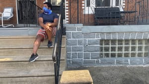 One year later, on a different stoop, and unsure if things have changed. (Photo by Holly Yokley.)