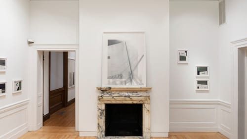 A white art gallery with elegant molding at floor and ceiling, and wood floors. It has black-and-white graphite art works.
