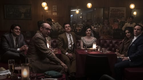 A scene from the movie. Six cast members sit in a dark, mirrored, wood-paneled bar, in a large leather booth.