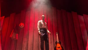 Actor Lawrence Stallings wears a shirt, pants, and suspenders on a smoky, red-lit stage with a wooden floor and backdrop