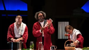 A scene from Minor Character: three actors, wearing large red cardigans, seem to be prepping dinner on a long wooden counter