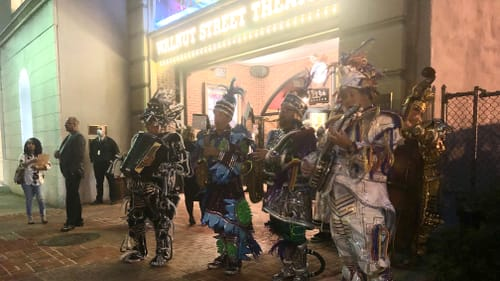 Four Mummers musicians, wearing shiny, sequined, feathery costumes, play at dusk outside the Walnut Street Theatre.