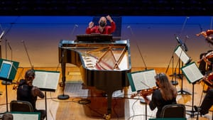 Nézet-Séguin sits at a grand piano, pausing play to conduct orchestra members, grouped around him, with his hands