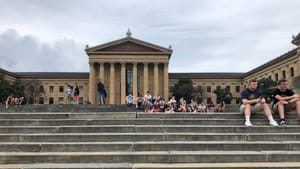 The Art Museum, with its giant east stairway large in the foreground. Higher up, people sit in groups on the steps.