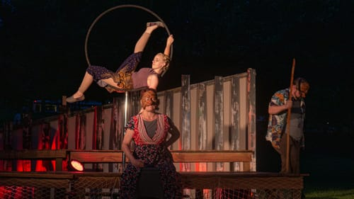 On a dark outdoor stage, a person in a mask stands in front of an acrobat posing inside a hoop suspended in the air.