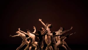 9 dancers in a circle around 1 male dancer arch their backs & throw their arms up ecstatically in skin-matching costumes
