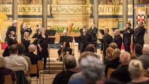 13 singers and musicians, all dressed in black, perform on the gold-painted, pillared chancel of a church full of listeners.