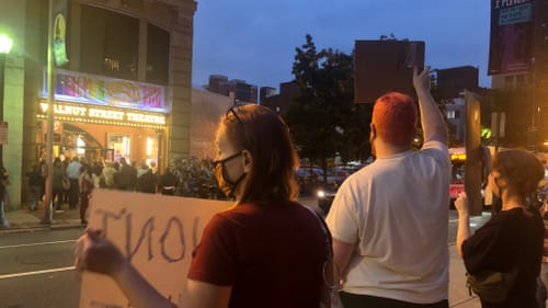 A view from behind the sign-waving protestors, with the crowded, lit-up theater opening visible across the street.