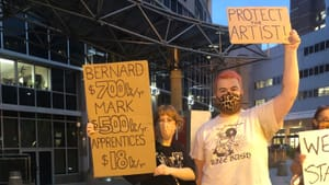 Two white protesters hold handwritten cardboard signs comparing inequitable theater salaries and the words Protect the Artist