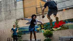 An action shot of QvK, with two actors, a Black woman and white man, leaping high in the air while swinging fencing swords.