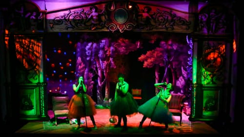 Three women in knee-length gowns on a colorfully lit stage sing into microphones like rock stars
