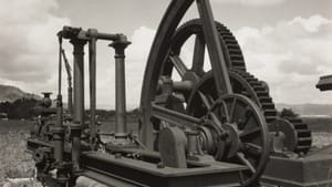 A black-and-white print of a giant metal machine with arms, pillars, and wheels. It's outdoors under a partly clouded sky