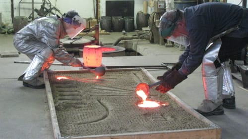 Fresh metal: Gina Michaels (left) and John Phillips work together on open-sand casting. (Photo courtesy of Gina Michaels.)