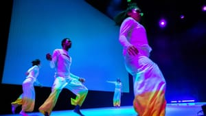 Four dancers move on a blue-lit stage wearing loose white garments with yellow and orange color from the knees to the ankles