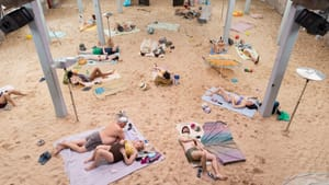 About 20 people dressed for the beach lie on a sandy, brightly lit beachscape created inside a large industrial building.