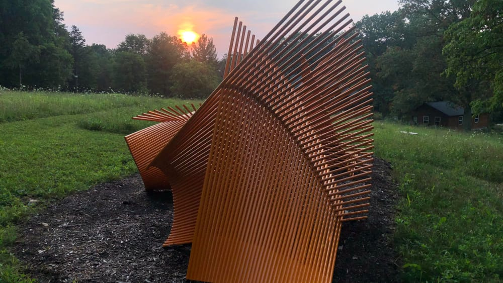 A graceful, rust-colored outdoor sculpture with undulating, overlapping lines sits among greenery, with the sunset behind it