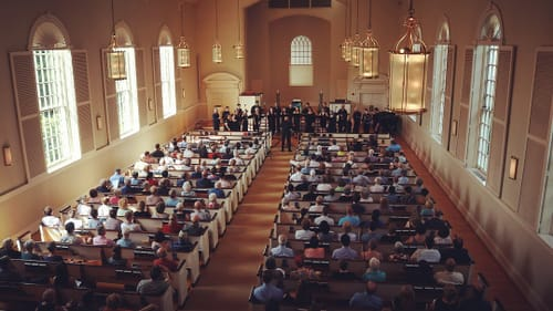 An aerial view from the upper rear of a church, people crowded in all of the pews listening to a choir sing up front.