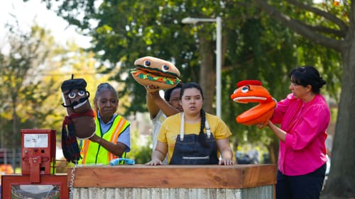Four actors hold a total of three large hand puppets: an éclair, a banh mi, and a macaron. They're performing in a park.