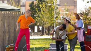 Vernal Belch, played by Pax Ressler in orange shirt and pink pants, intimidates three other characters on a stage in a park.